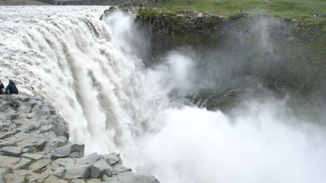 Two people enjoying on the mighty  Dettifoss  waterfall  in Vatnajökull National Park, Iceland  in summertime