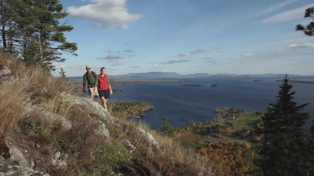 WS TU HA Two people hiking on Mt Kineo with Moosehead Lake in background, Maine, USA