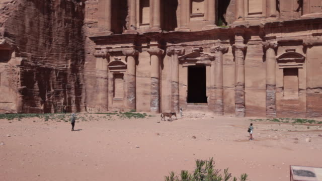 Two people in front of Al Deir (Monastery) in Petra, Jordan