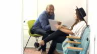 Two people in office talking, looking at digital tablet