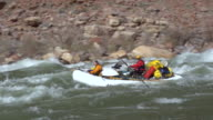 WS PAN ZI Two people in white raft floating down rapid and rocky shore in background / Grand Canyon, Arizona, USA