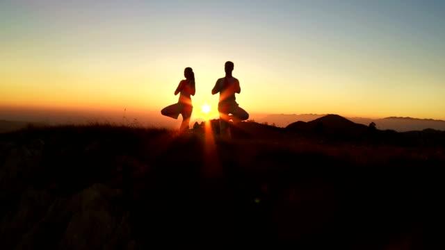 HD: Zwei Personen üben Yoga auf der Ridge