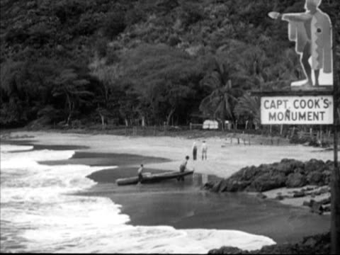 Two people pulling canoe onto sand w/ two people walking beach 'Captain Cook Monument' sign BG TU WS People one possibly park ranger looking at...