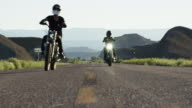 Two people ride motorcycles down highway, low angle, slow motion