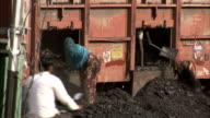 Two people shovel coal out of a freight train wagon.