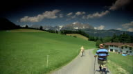 Two people walking separately up paved road boarding foothill meadow leading to chalet home Austrian Alps mountains BG Excursion sightseeing holiday...