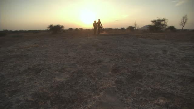 WS POV Two people walking towards sun in early morning / Tanzania