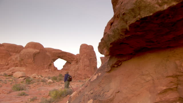 Two photographers at dusk with North Window Arch and South Window Arch in the distance