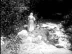 1955 B/W REENACTMENT WS Two pilgrim women cleaning clothes in stream / AUDIO