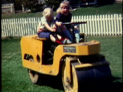 Two playful girls (2-3, 4-5), driving small steamroller in garden, Middlebury, Vermont, USA