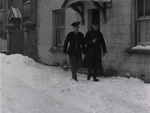 Two policemen walk along a snow covered street in Princetown Devon