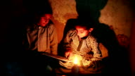 Two poor rural girls studying in lantern at home