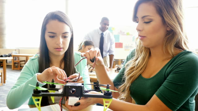 Two pretty Hispanic teenage girls work together to create robot at STEM school
