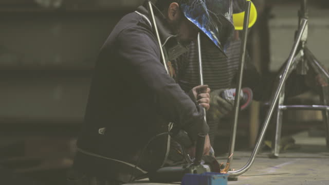 Two repairmen grinding metal with electric saw in a workshop.