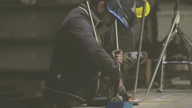 Zwei Mechaniker Schleifen Metall mit elektrischen Säge in einer Werkstatt.