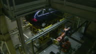 Two robotic arms work on an SUV on an assembly line in an automobile factory.
