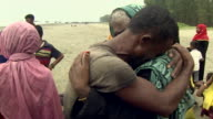 Two Rohingya refugees who fled persecution in Burma embracing after reaching Bangladesh