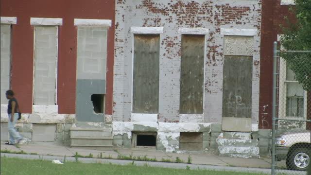 HD Two row houses in state of disrepair flaking paint boarded windows doors woman walking up sloped sidewalk Foreclosure subprime lending reverse...
