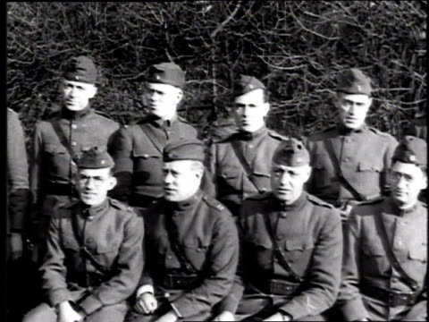 Two rows of soldiers in dark dress uniforms posing for camera one row standing behind seated row / France
