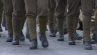 Two rows of soldiers legs marching on paved walkway calves in leg green wraps puttees black boots on feet halting stopping starting burlap sandbags...