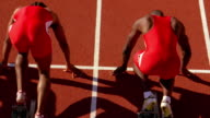 Two runners sprint out of starting blocks at the beginning of a race.