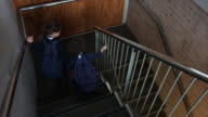 Two school sister girls walking down stairs together