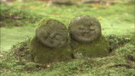 Two seated Buddhist stone statues covered in moss