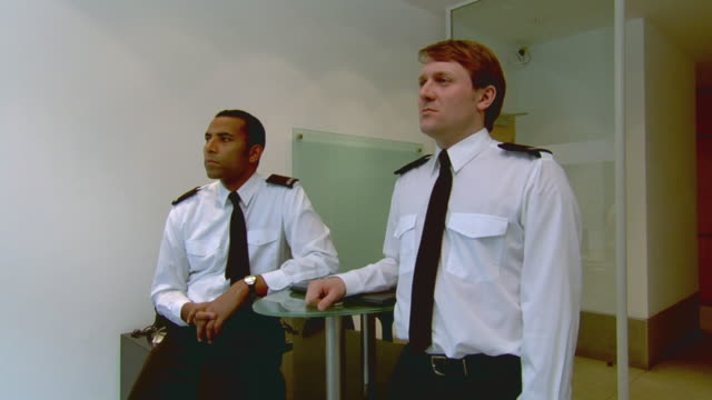 MS Two security guards standing and turning to look at camera / London, England