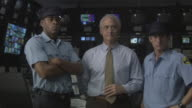 MS Two security guards standing with businessman in television studio control room / Culver City, California, USA