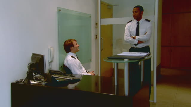 WS Two security guards talking face to face in office then turning to look at camera / London, England