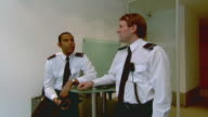MS Two security guards talking face to face in office then turning to look at camera / London, England
