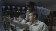 MS Two security guards watching surveillance monitors with businessman in television studio control room / Culver City, California, USA