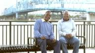 Two senior black men on park bench laughing