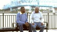 Two senior black men on park bench talking