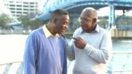Two senior black men talking, laughing outdoors