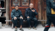 Two senior Chinese adults sitting on a bench
