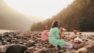 Two senior couple drinking coconut water at riverbank, Ganges River, Rishikesh, Uttarakhand, India