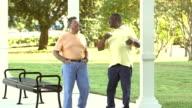 Two senior men on bench, get up, walk, talk