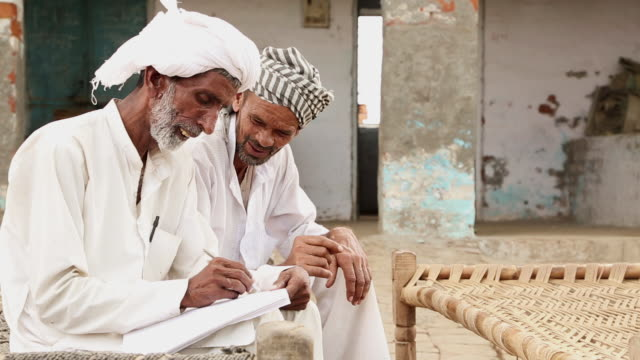 Two senior men studying, Haryana, India