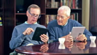 Two senior men talking, using digital tablets