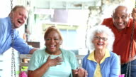 Two senior multi-ethnic couples laughing at camera