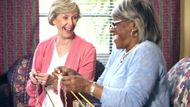 Två äldre kvinnor stickning, chatta