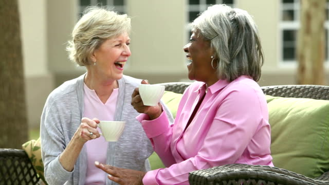 Two senior women on patio talking, drinking coffee