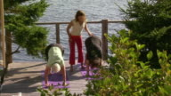 WS HA Two senior women with instructor practicing yoga on deck by sea, Halifax, Nova Scotia, Canada