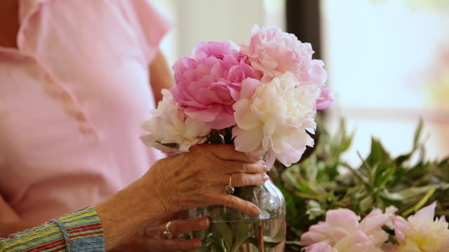 'MS TU Two seniors citizens arranging flowers in flower pot and talking  / Laguna Woods, CA, United States '
