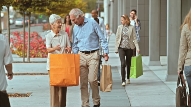 SLO MO of two seniors walking down the shopping alley