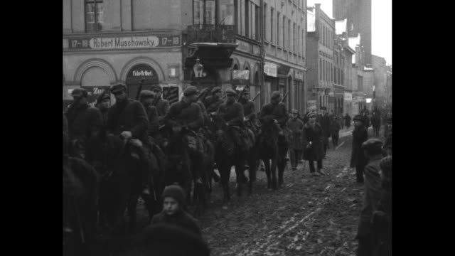 Two shots of armed Lithuanian volunteers riding in cars and marching on foot past camera in Memel East Prussia / Lithuanian cavalry marching down...
