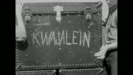Two shots of crates of supplies stacked on deck of USS Saidor / CU footlocker with word 'Kwajalein' painted on side / forklift driving across deck...