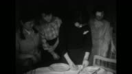 Two shots of female instructor standing at table showing Japanese women standing around table how to set table / Japanese woman setting table while...