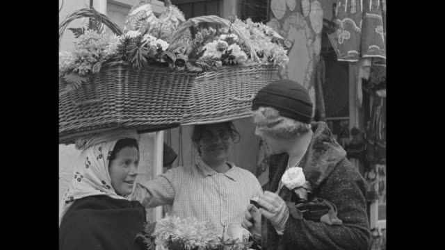 Two shots of female passenger buying flowers from native woman with large basket full of flowers on her head during RMS Empress of Britain's stop in...